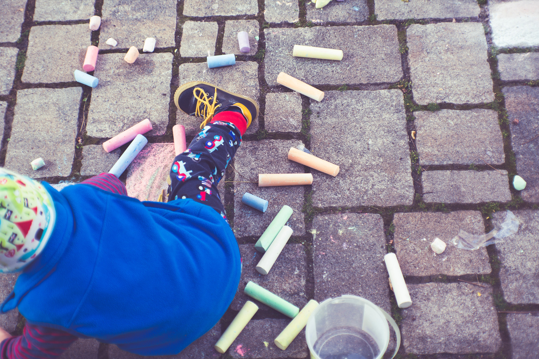 Child drawing with coloured chalk on sidewalk