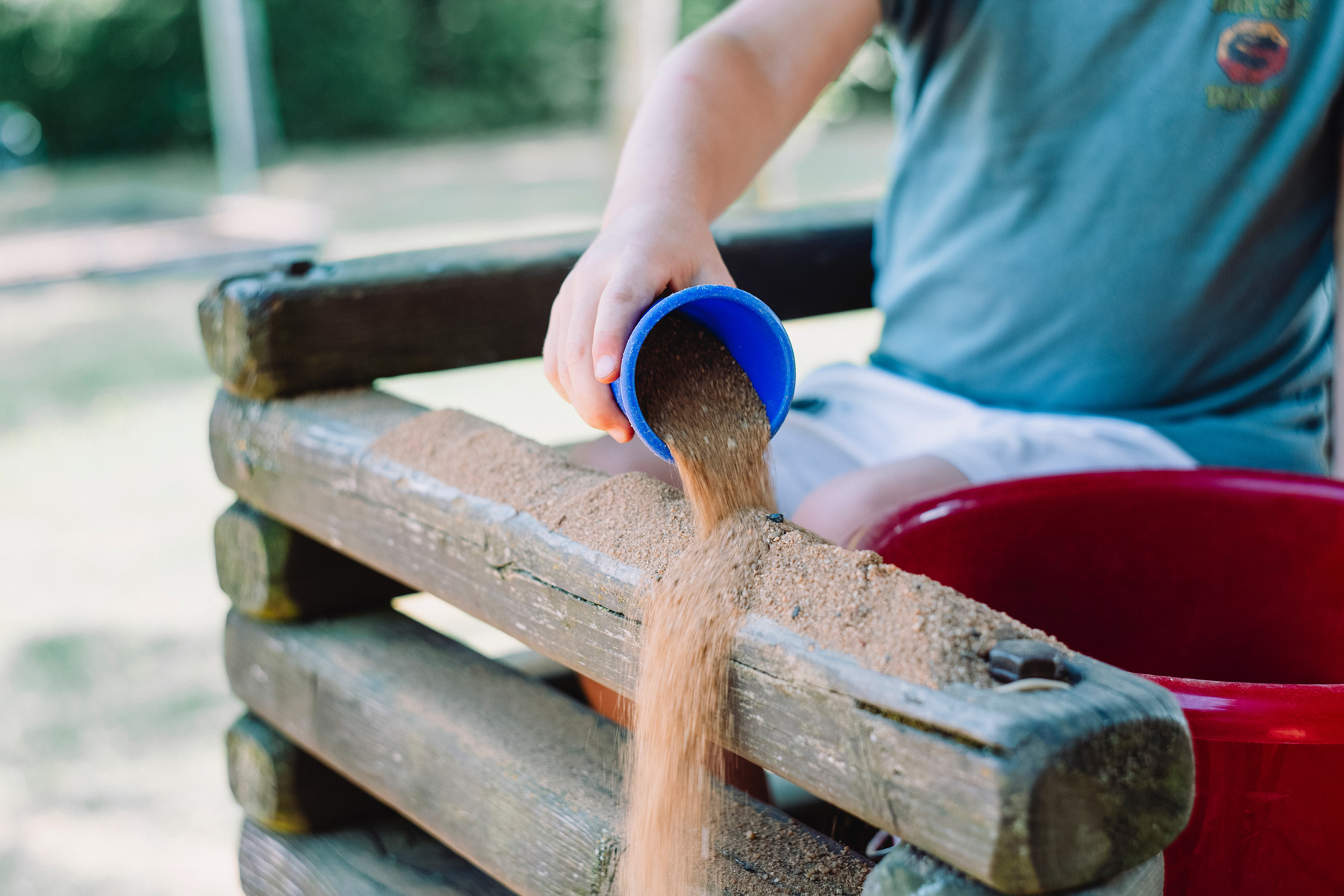 Kid puring sand onto a log with a blue cup